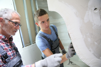 Young apprentice with professional plasterer